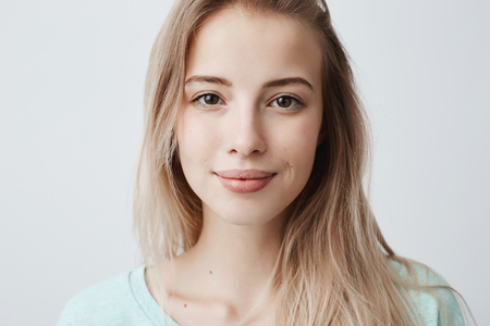 Beautiful female having dark shining eyes, pure skin and blonde straight hair wearing loose sweater looking directly at camera having mysterious and glad expression. Face expressions and emotions Stock Photo