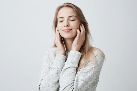 Nahaufnahmeporträt der schönen attraktiven europäischen jungen Frau in der grauen losen Strickjacke, entspannend mit den geschlossenen Augen und hören auf ihre Lieblingslieder über weiße Kopfhörer und verwenden Musik-APP. Standard-Bild