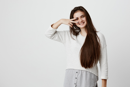 Emotional beautiful girl with long dark hair dressed casually, showing v sign, smiles joyfully, posing against gray wall. Young brunette female having fun indoors, expressing positive emotions.