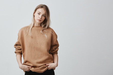 Cute pretty beautiful woman wears loose sweater and black trousers, holds her hands in pocket, looks with appeal at camera. Pleasant-looking girl posing against gray background