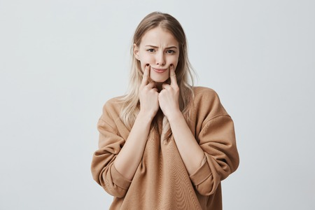 Studio shot of beautiful blonde woman making grimace, touching her cheeks with fingers, making herself smile, frowning face, being displeased and upset. Face expression and negative emotions