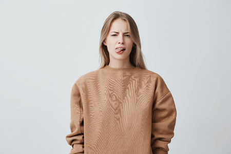 Naughty beautiful girl with blonde long hair in beige sweater misbehaving, sticking out tongue at camera as a sign of disobedience, protest and disrespect. Emotions, reaction, feelings and attitude