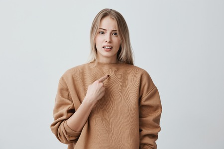 Shot of beautiful blonde woman being accused of something she didn`t make, pointing with index finger at herself, frowning face, being displeased and angry. Face expression and negative emotions Reklamní fotografie