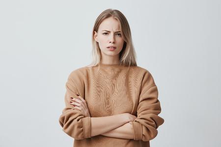 Portret pięknej dziewczyny z prostymi blond włosami marszczącymi brwi z niezadowoleniem, ubrana w luźny sweter z długimi rękawami, z założonymi rękami. Atrakcyjna młoda kobieta w zamkniętej postawie. Zdjęcie Seryjne