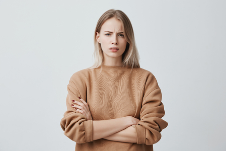 Waist-up portrait of beautiful girl with blonde straight hair frowning her face in displeasure, wearing loose long-sleeved sweater, keeping arms folded. Attractive young woman in closed posture. Stok Fotoğraf - 93873312