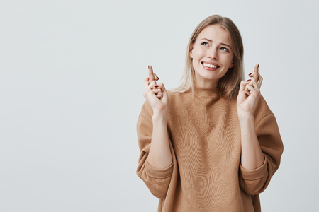Indoor shot of blonde student girl dressed in beige sweater, crosses fingers and has great hope for better, poses against gray background. Young female student wishes fortune before exam Stock Photo