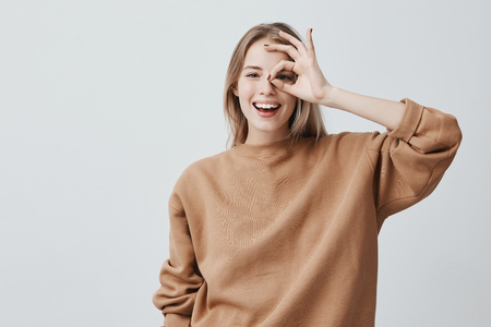 Positive funny blonde girl in casual clothes shows ok sign, laughs at camera, demonstrates that everything is fine, agrees. Cheerful woman gestures indoors. Body language and human emotions Stock Photo