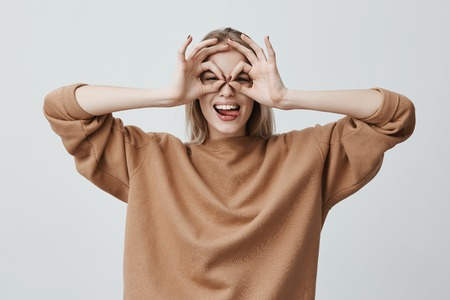 Cheerful excited female with blonde long straight hair showing Ok gestures with both hands, pretending to wear spectacles, and smiling broadly, enjoying her carefree happy life