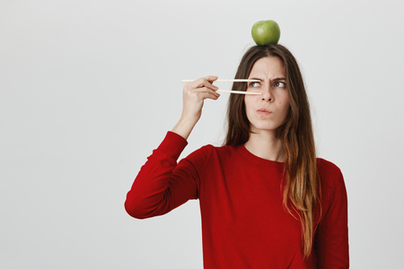 Emotional clueless young female with long hair dressed in red sweater with green apple on head having dissatisfied puzzled look, frowning face in displeasure. Emotions, feelings and face expression
