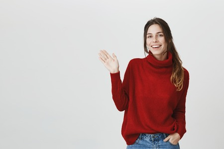 Young attractive student with beautiful long brown hair smiling broadly, waving showing hello gesture over white background. Pleasant attractive girl came to her work, greeting coworkers cheerfully. Archivio Fotografico