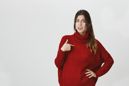 Portrait of young beautiful european girl looking confused being accused in something, pointing at herself wearing trendy red sweater. Girlfriend can not believe her boyfriend blames her