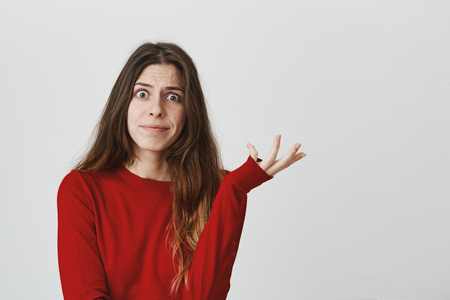Portrait of attractive caucasian woman in red top looking with popped eyes showing so what gesture over white background.