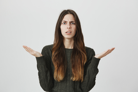 Portrait of unhappy confused and questioned attractive young girl holding her palms up, isolated over white background. Woman has no clue why her boyfriend is angry at her. Stockfoto