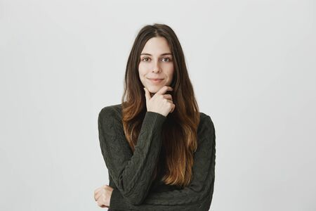 Attractive european female with long brown hair, smiling and holding hand on chin while thinking about something, isolated over white background. Young designer have new ideas for her project