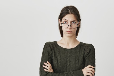 Indoor portrait of young woman in spectacles has serious confident expression, keeps arms crossed, feels angry after quarrel with colleagues. European irritated female looks dissatisfied