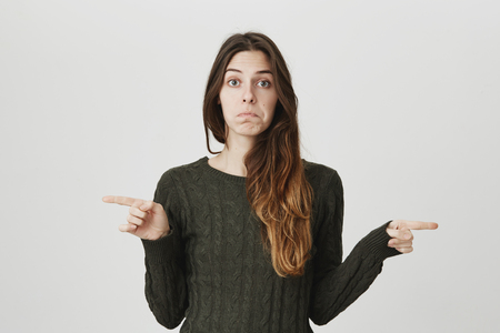 Waist-up portrait of attractive young girl with sad and disappointed expression, pointing index fingers in both sides, isolated over white background. Woman confused, dont know what to do Stock Photo