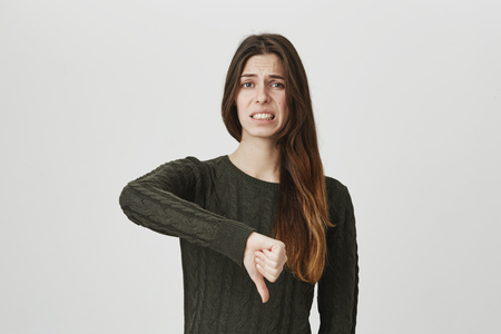 Portrait of dissatisfied frowning girl with long hair in casual clothes giving thumbs down gesture, expressing her disapproval and dislike of something. Negative emotions, reaction and feelings