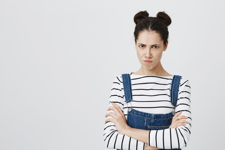 Picture of funny brunette girl in denim overall posing at studio, keeping arms folded, having offended look, pouting lips, showing her dislike, negative attitude and reaction. Stock Photo