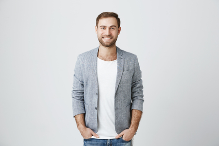 Delightful european man wearing jacket over white t-shirt and jeans, looks pleasantly at camera, has good mood as comes home after work. Fashionable pleasant looking male entrepreneur Stock Photo
