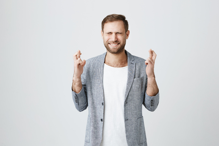 Handsome stylish bearded male entrepreneur with trendy haircut standing with crossed fingers and closed eyes, frowning his face, having pleading expression asking for good luck at his new project
