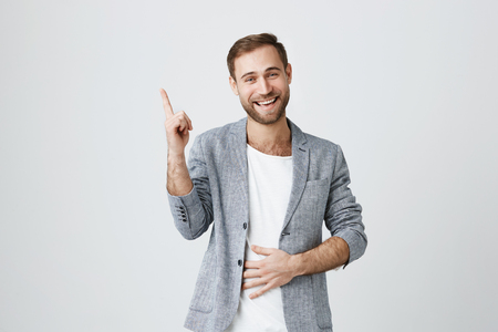 Good-looking happy positive shocked bearded European male dressed in trendy jacket pointing his index finger upwards, showing something interesting on it. Human facial expressions and emotions