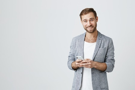 Joyful Caucasian handsome man with stubble dressed stylishly using mobile phone, surfing internet. Happy smiling guy in stylish clothes using wifi on cell phone