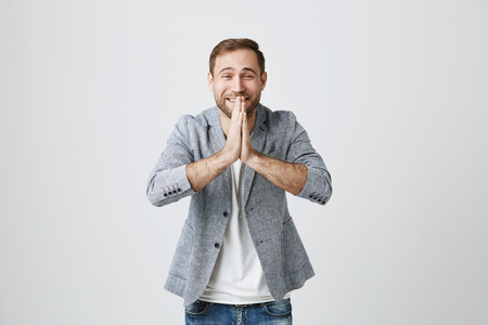 Happy bearded attractive male with blue eyes keeps palms pressed together, concetrated on his wish or great desire, asks for something important, smiles at camera and believes dreams will come true Stock Photo
