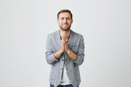 Isolated shot of bearded handsome male wears fashionable clothes, keeps palms together as prays for good luck, has sad unhappy expression, isolated against gray background. Facial expression