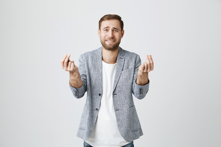 Attractive male with beard gestures actively, hopes for fortune during special event or occasion, asks for something, isolated against gray background. Face expressions and body language Фото со стока