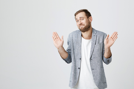 Cheerful stylish fashionable bearded guy in trendy jacket over white t-shirt raises hands as shows being uninvolved, has happy look. Caucasian male gestures in studio. I am not guilty! Banque d'images