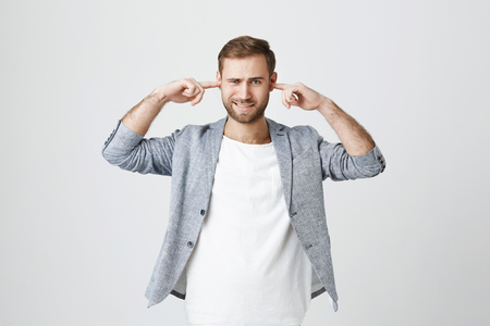 Stressed man with beard plugs ears, avoids loud sounds at street, doesn`t want to listen noise, isolated against gray background. Bearded man ignores something unpleasant, frowns face