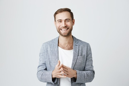 Successful prosperous bearded businessman dressed in stylish clothes, has good mood after signing profitable agreement with partners, rejoices terms of contract. Success concept