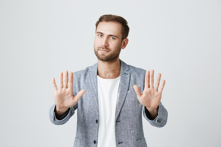 Good-looking bearded stylish man shows palms, demonstrates absence of responsibility, isolated against gray background. Handsome young male raises hands, looks puzzled, feels guiltless. I give up!