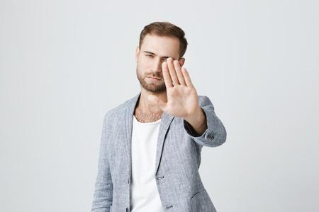 Ernster überzeugter verärgerter europäischer Mann mit dem Bart, der die stilvolle Kleidung aufwirft gegen graue Studiowand trägt und Hände in der Endgeste hält, als ob das Sagen: Bleiben Sie weg von mir. Körpersprache.