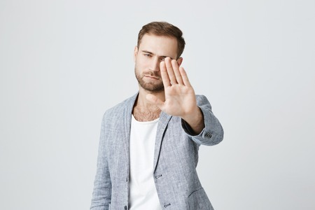 Serious confident angry european man with beard wearing stylish clothes posing against gray studio wall, keeping hands in stop gesture, as if saying: Stay away from me. Body language.