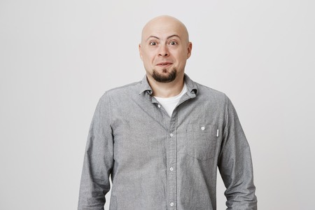 Portrait of bald mature man with beard looking surprised and amazed at camera while standing over white background. Adult wearing casual clothes, stunned. He did not expect to see his friend. Stock fotó