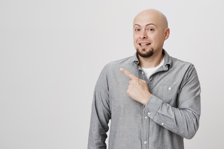 Advertisment, emotions and body language concept. Attractive young bald man with beard point his finger away over white background. Person smiles looking cheerful showing something to his wife.