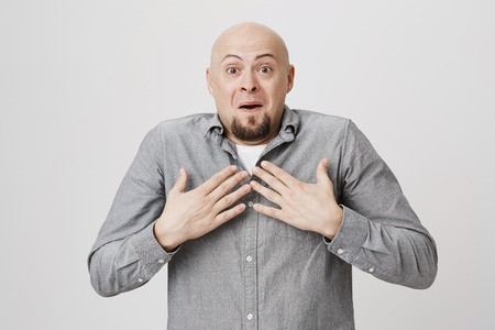 Picture of attractive male with funny, shocked and surprised expression holding his hands on chest over white background. Handsome bearded guy just found out that he won in lottery looking happy.