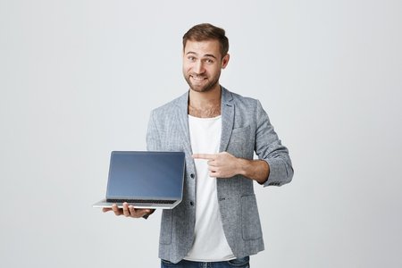 Stylish male enterpreneur with thick beard and trendy hairstyle posing against gray studio background with laptop in hands, smiles at camera, points at screen, demonstrates how good this device is.