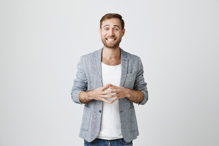 Confused unshaven male model in trendy gray jacket clenches teeth, frowns face in shock and bewilderment, being stressed to hear bad news, isolated against gray wall. Stock Photo