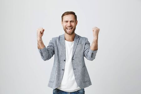 Lucky overjoyed bearded male winner in stylish clothes clenches fists, rejoices triumph at work, glad to recieve high profits, has own prosperous business. Attractive european man achieves goals