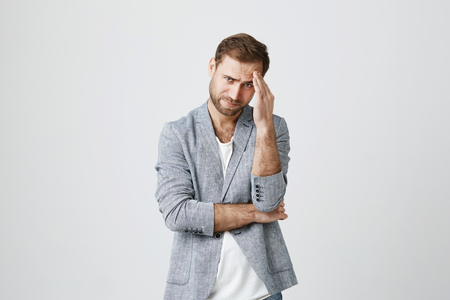 Stressed out frustrated caucasian man dressed in trendy clothes, frowning face because of noise, holding hand on his forehead because of pain. Negative emotions, stress headache and frustration. Stock Photo