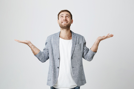 Photo of pleasant looking male with beard dressed in trendy clothes looks dreamfully upwards, imagines something positive. Isolated shot of attractive man isolated against gray background