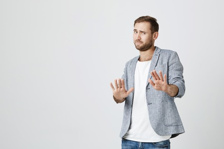 Attractive bearded man makes frightened gesture with palms, defends himself from someone, asks to stop it immediately. Guy says stay away from me, shows stop sign. Body language concept Фото со стока