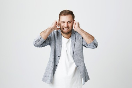 Irritated handsome bearded male with displeased facie expression, plugs ears, clenches teeth, expresses negativeness, avoids noise, isolated against gray background. Stop this annoying sound!
