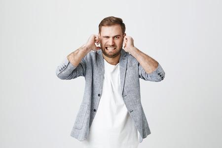 Apuesto macho barbudo irritado con expresión de rostro disgustado, tapones de orejas, aprieta los dientes, expresa negatividad, evita el ruido, aislado contra el fondo gris. ¡Pare este molesto sonido!