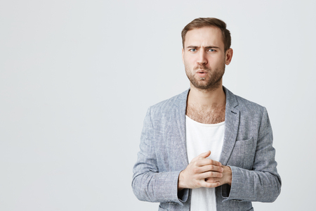 Puzzled bearded male has unhappy look, frowns face in bewilderment, wears trendy jacket isolated against gray background. Negative emotions, face expression and feelings