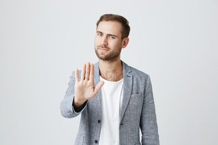 Angry bearded male model gestures indoors, shows stop sign with palm, refuses to do something, isolated against gray studio background. Serious bearded irritated man shows stop gesture indoors