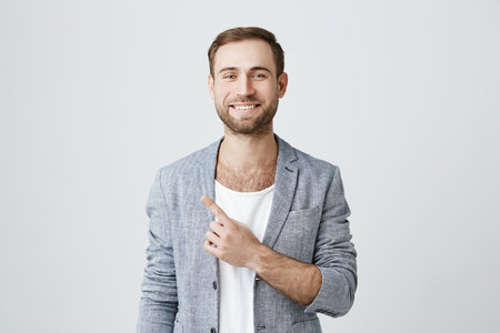 Positive attractive bearded man smiling broadly at camera and pointing finger away, showing something interesting and exciting on studio wall with copy space for your text or advertising content
