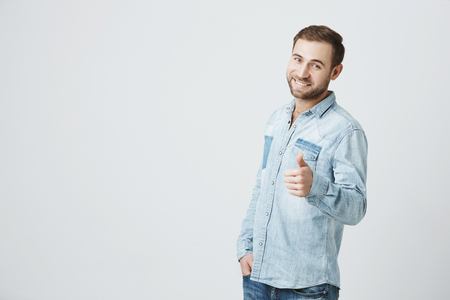Young man holds his thumb up. Smiling happy bearded hipster man in denim shirt, showing thumb up sign to camera, approving good job. Positive emotions, feelings and face expression Stock Photo